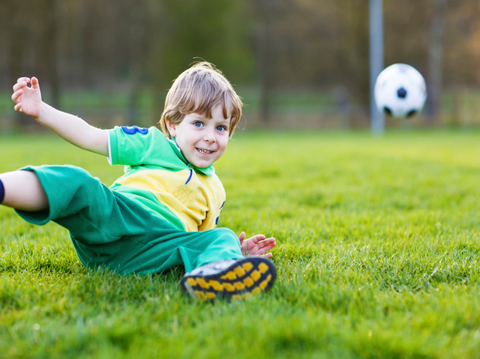 Blond boy of 4 playing soccer with football onl field