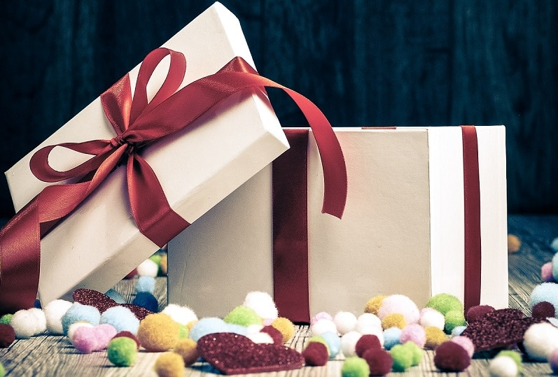 Open gift with colorful balls on wooden background